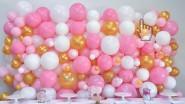 Стена из разноразмерных белых, розовых и золотых шаров
